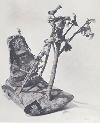 """The """"Weaving Lady"""" seated at her loom under a pacay tree. The tree is 18 inches high from base of the pillow, which is 13 inches long."""