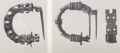 Two Phrygian bronze fibulae of the late 8th century  B.C. found at Gordion.  The fibula with the studs is of the same type as the one found in Italy which is discussed in the text. The second fibula has a lock-plate to mask the double pins. The semicircular-shaped arcs and the distinctive horned catches are characteristic of Phrygian fibulae, Lengths: 5cm.; 6.7 cm.