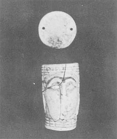 """Two miniature cosmetic capsules with their lids, each 1 ½ inches high, of frit with a green glaze. The one to the left imitates a Mitannian seal design: two stags on either side of a palmettte tree fill one side and four figures in procession advance toward the left on other.  The capsule on the right is decorated with rosettes alternating with bands of guilloche. In the center of the picture is a small glass amulet (3/4 inch) moulded in the form of a human face, perhaps representing the goddess Ishtar.  Below it is a couchant lion, 1¾ inches long, in quart-frit ware with remnants of yellow glaze, found in the """"souvenir shop."""""""