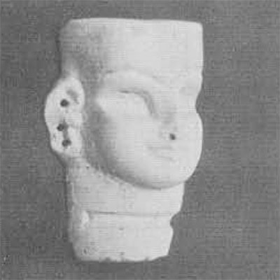 A large white frit female mask with traces of green glaze, 3 inches high. The eyebrows and large sockets for the eyes are grooved for inlay; there is also a groove for an inlaid necklace. The finely modelled mouth suggests a date in the 14th-13th century B.C.