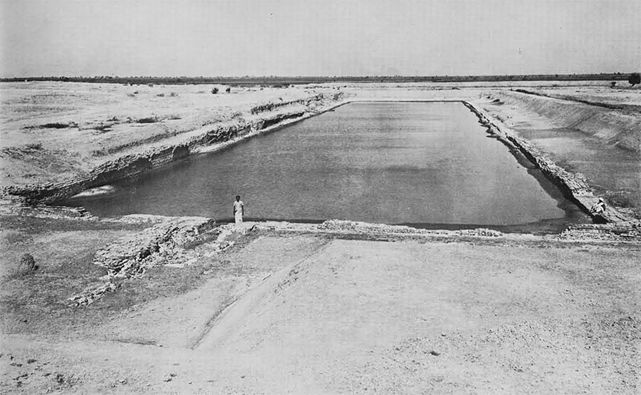 The dock at Lothal. The figure in the foreground is standing near the spillway; the figure on the right is sitting in the inlet of the second stage.