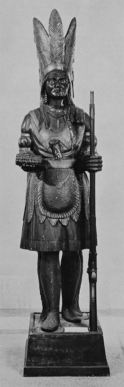Indian Chief with Rifle. From the White Collection, lent by Mrs. James Reswick. Height 77 inches, with base 87 inches. There are several reasons for associating this figure with the work of Julius Melchers or one of the carvers whom he trained, The head of a similar wooden Indian named Big Chief Me-Smoke-Em was modelled after an Iroquois chief, with conventional pose ans costume. The son of the original owner said Me-Smoke-Em was made by one of the world's great carvers. Melchers was a great carver by cigar store store standards, he did use real Indian models, and a known work does show that his figures from the head down are conventional. Since it is known that Melchers had apprentices it is possible that he may have modelled heads and his  assistants did the rest. This figure would not deny such conjecture, as the head and feathers are unusually modelled   and resemble those of an Indian rather than a white man while pose and costume are of the usual conventional form.