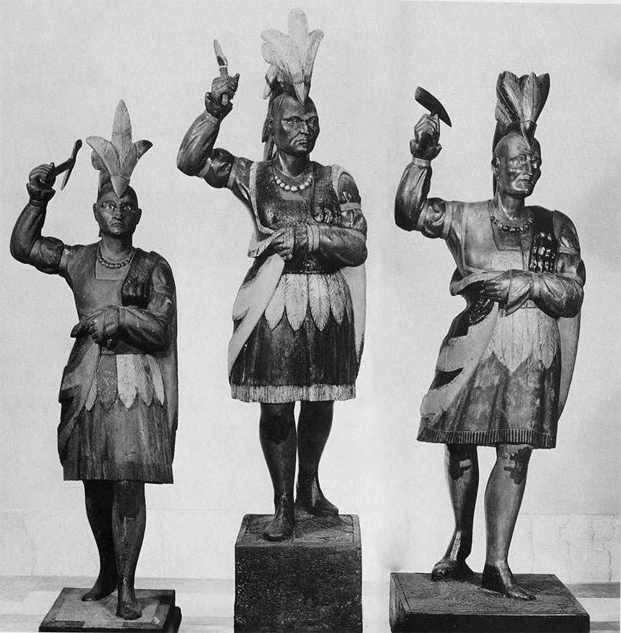Three Indians with Tomahawk. The one at the left from the White Collection, lent by Mrs. James Reswick, the other two lent by Mr. Alfred E. Bissell. Heights: 64 inches, with base 71 inches. 66 inches, with base 84 inches; 67 inches, with base 77 inches. According to Jean Lipman in her book on American folk art, The Indian at the left is one of the few known to have been made by a figurehead carver, John L. Cromwell. Characteristic of the work of the figurehead carver, are the windblown cloak and headdress and the slightly uplifted face with an outward searching gaze. It is conceivable that the other two figures are also the work of Mr. Cromwell; certainly they must have come from his workshop. The only differences are the slightly larger scale and and variations in the tobacco-leaf kilt. Two more examples are known from photographs, and one Indian figurehead said to have been made about 1836 and later used as a Cigar Store Indian is also identical to these others.