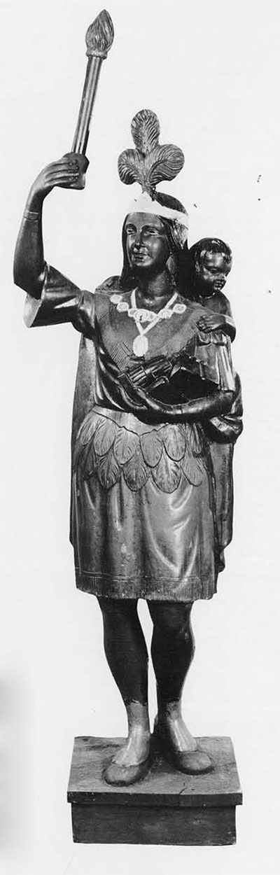 Zinc Mother and Papoose. Lent by the Atwater Kent Musuem. Height 62 inches, with base 68 inches. Other versions of this figure exist, painted in different colors, and holding a bundle of cigars. The torch in fact is made of wood and inserted with screws through the fingers and thumb. Perhaps the model was cast empty-handed for the buyer to choose his own accessory. Some critics say that metal Indians lose something of the charm and individuality of the wooden version; however, once a good Indian, such as this one, was cast, it did not suffer from the incompetency of lesser carvers. Typical of many Cigar Store Indians, the facial features are more Caucasian than Indian.