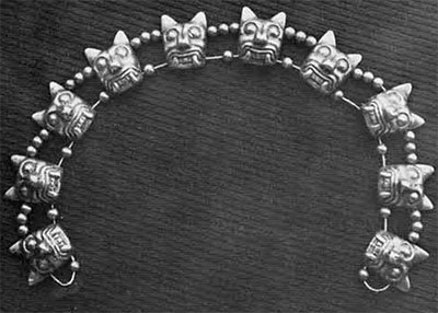 Gold necklace of beads and jaguar heads, found in Burial 27-A.