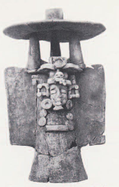 """Late Preclassic pottery incense burner with the modeled face of the Maya """"old god"""" recovered from a ceremonial cache within the ramp of Mound 1."""