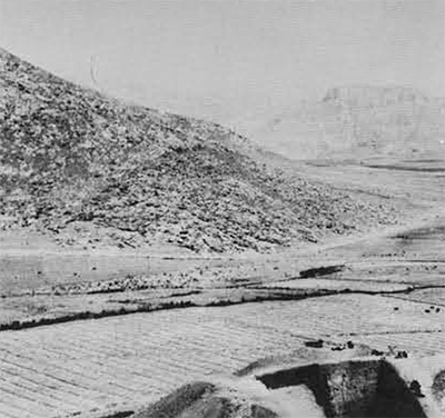 The site of Ganj Darch Tepe  near Harsin in southern Kurdistan, showing  the author's excavations as of 1969. In the distant background is Behistun Mountain. The site was probably occupied about 8500 and 7000 B. C.