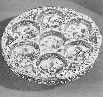 A Persian silicious glazed sweetmeat dish in brown luster, having seven symmetrical depressions, the center one with an inscription in late 12th century Cufic and the surrounding six in Saracenes arabesque with figures clothed in the style of the Sassanid dynasty. Diameter, 33 cm. Museum Object Number: 319259