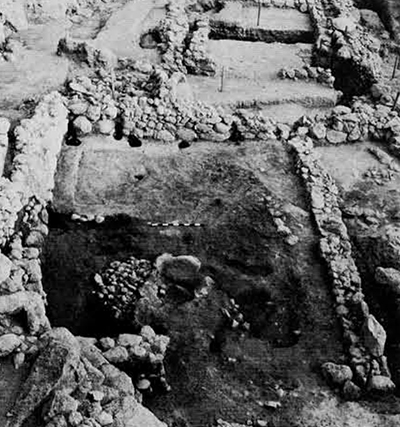 """""""The Blacksmith's Shop"""": Earliest period of Structure III, Showing open forecourt with central hearth and roofed area behind. Wall running diagonally across the left is a later terrace wall, in the background is part apsidal Structure I."""