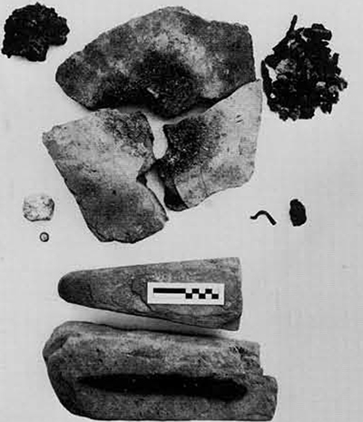"""Metalworking at Pithekoussai. Clockwise from the upper left: Sponge-like lump of iron """"bloom"""" ; large, course sherds from Structure III floor burned by a bellows-fed fire until vitrified at center; fragments of iron and slag associated with sherd hearth; small piece of a  bronze ignot (?); miscast bronze fibula; whetstones from Structure IV with an iron knife on the lower one; bronze and lead disc-shaped weight; lump of lead."""