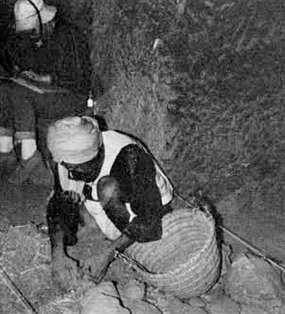 Excavation of disturbed debris in the burial tunnel of Bekenkhons, using face masks with dust filters to facilitate breathing.