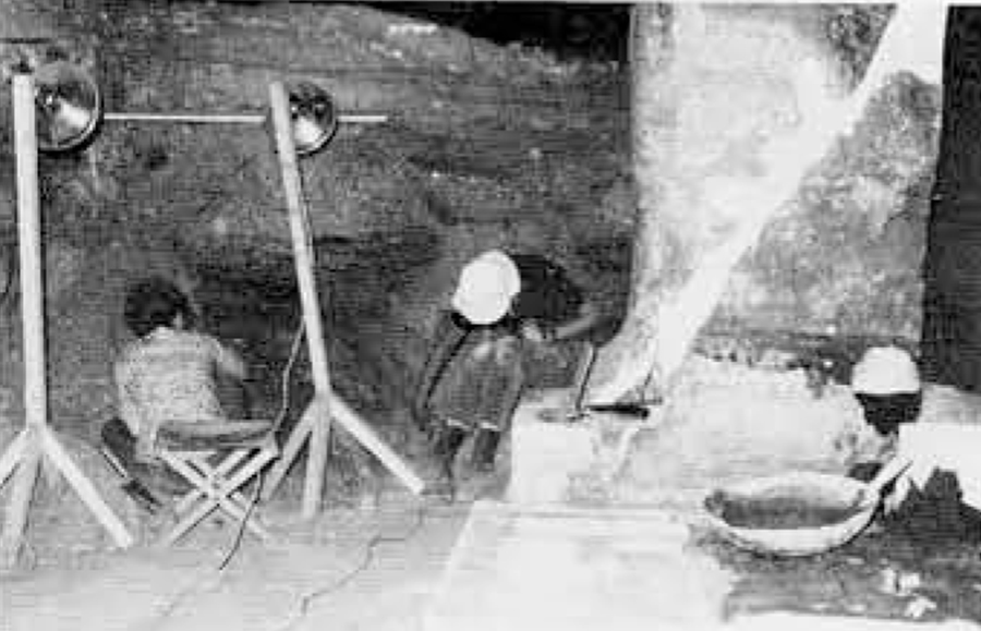 Examination of the stratified deposit in the broad-hall of the tomb of Nebwenenef, while repair and rebuilding of its pillar proceed.