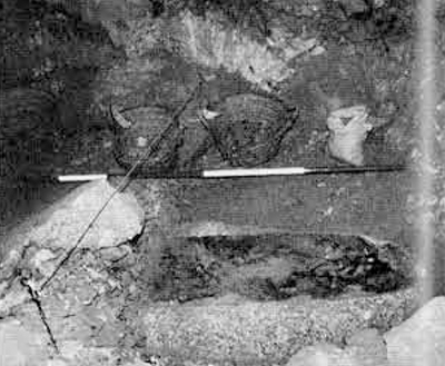Fragments of a red granite sarcophagus from the tomb of Bekenkhos: a large piece of the base still in situ in a shallow depression in the floor of the burial chamber during excavation (the photographic scale, as used also elsewhere, is two meters long).