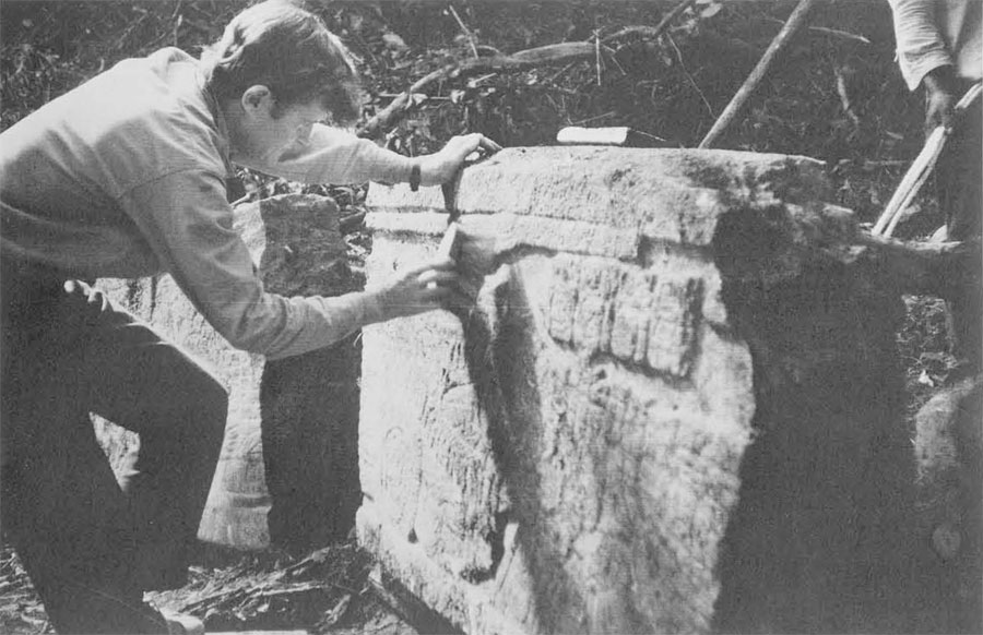 Ian Graham of Peabody cleaning front of stela in preparation for photographing it. He hopes to photograph and draw all remainign examples of Maya sculpture and writing before all are stolen or damaged by weather.