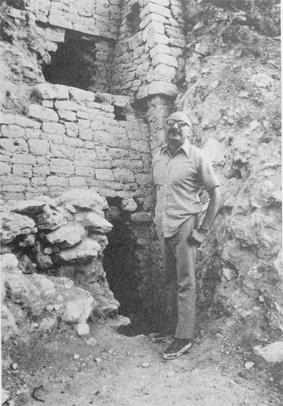 Victor Segovia, Mexican archaeologist, stands in front of holes dug by looters in side of Maya pyramid at Kohunlich, remote jungle site in Quintana Roo area of Mexico (on Yucatan peninsula)