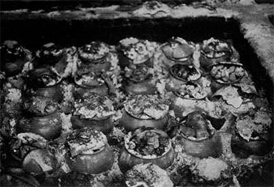 Heat treatment of agates before they are chipped. Nodules are placed in small pots along with sawdust which is then lit and allowed to burn slowly