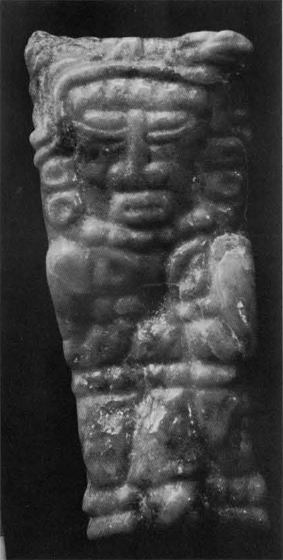 Roughly rectangular pendant from Burial 23, North Acropolis, Tikal. Light green or gray jade. Middle Classic. The front shows a frontal standing figure with arms folded upwards. The back of the pendant has twelve incised glyphs in two vertical rows of six each.