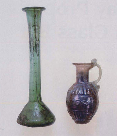 Left: Second century AD candlestick unguentarium composed of transparent green glass (MS5518). Right: Second century AD mold-blown vessel composed of transparent purple glass (MS5013)