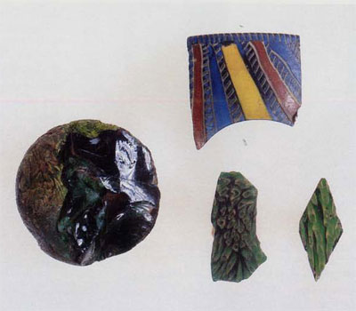 Left: The glass ball (MS5566), with its interior revealed by a modern break. Note the air bubbles that were trapped between the re-fused pieces of glass. Upper right: A fragment from the rim of a straight-sided mosaic glass bowl (MS3369). The different strips of glass used in the manufacture of this piece are visible, including the bichrome twists. Lower right: On the left is a fragment from the base of a small glass bowl (MS545), used in mosaic or wall decoration. Both objects are made of the same type of millefiori glass: opaque yellow rods in a translucent green matrix.
