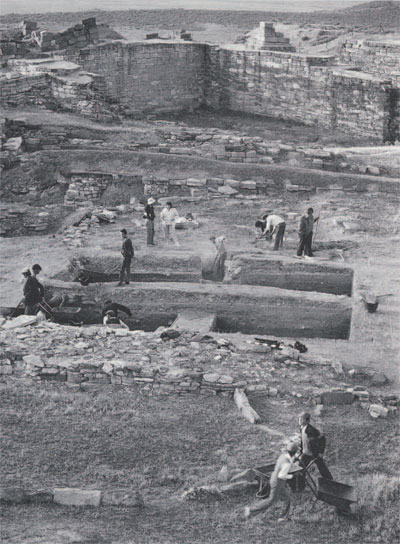 View of excavations at Gordion, 1989. Most of the standing architecture dates to the time of the destruction of the Early Phrygian city of Midas, ca 700 B.C. The trenches in the foreground are being dug beneath this level to uncover the Late Bronze Age settlement. in the ditance, the massive Early Phrygian gateway is capped by fragments of a similar gate marking the reconstruction of the site in the Middle Phrygian period (6th century B.C.). (Photo by Laura Foos, courtesy of the Gordion Project)
