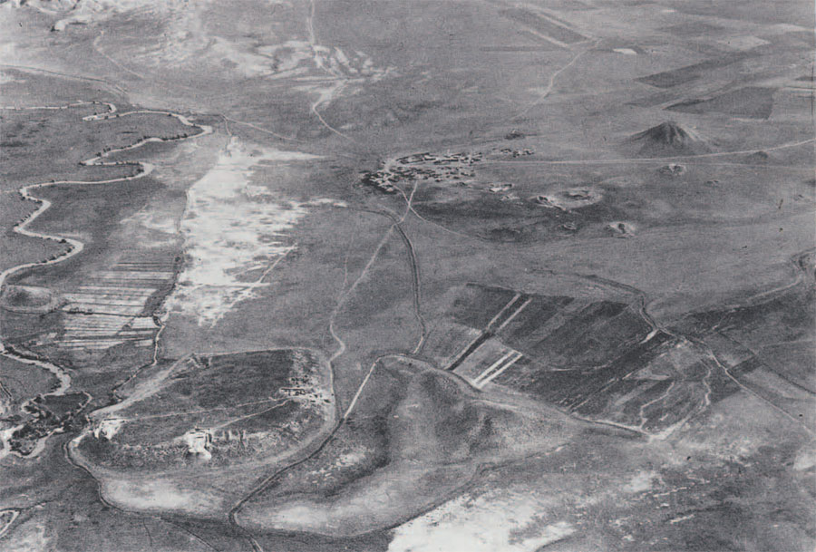 General aerial view of Gordion, 1950. The city mound of Gordion is located at the lower left, next to  the Sakarya (ancient Sangarios) River. The conical hill in the upper right is an artificial mound of earth, erected over a wooden tomb chamber (Tumulus MM). The body within the tomb may be that of King Midas. (Photo courtesy of the Gordion Project).