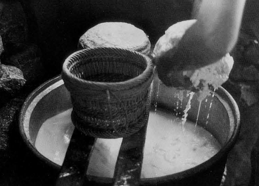Figure 10. Gathering curdled cheese from the cauldron. Baskets rest on the wooden frame.