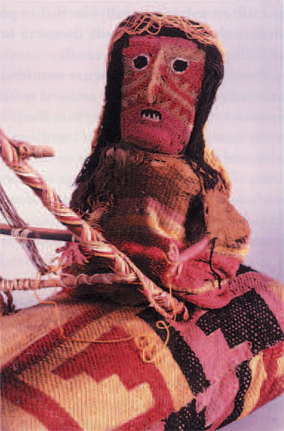 The weaving lady wears a woven garment and a twined openwork scarf. She sits on a pillow covered with a brocaded textile. The fabrics of the figure and pillow are supported by underlying bundles of leaves and plant fibers. The loom frame is made of lengths of reed decorated with plaited yarns, and the tree is fashioned from a bundle of reeds or grasses wrapped with yarn.