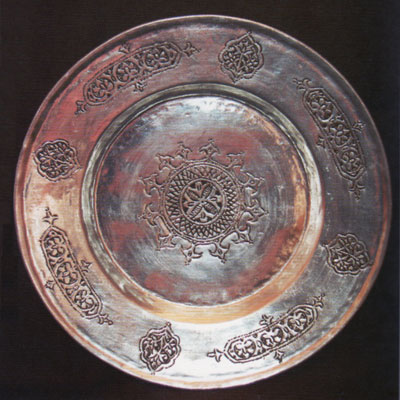 A bronze plate with scrolling decoration.