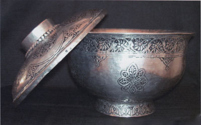 A bronze and silver tureen with lid, with rosette patterns.