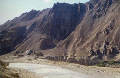 Paved roads in Ladakhi, running alongside a mountain.