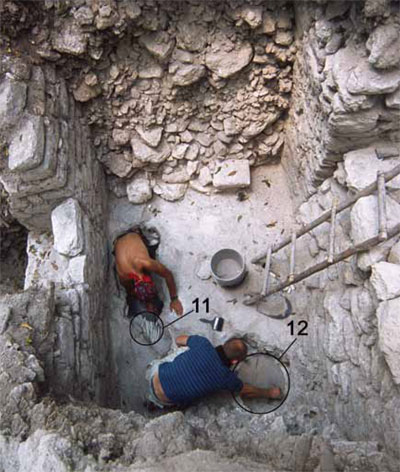 Archaeologists excavate the eastern chamber of the Structure 15 temple. Note the two offerings (11 and 12) deposited on the floor of the chamber.