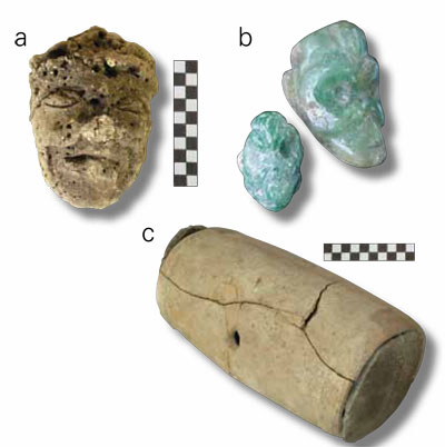 Numerous artifacts were found in two deposits excavated below Structure 99: a) a clay head represent- ing a Maya deity (of the Underworld?), b) two jade pendants with representations of monkey heads, and c) a possible beehive.