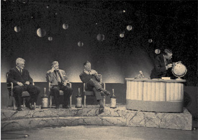The panel was seated at the opening and close of the show. Left to right:  Coon, Lipchitz, and Kidder, with Rainey at the desk. This set design was  considered innovative for the 1950s. Notice the balls in the background  suspended from the top of the set. UPM Image #140920.