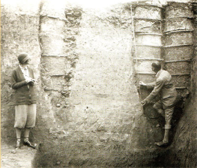 Katharine and Leonard Woolley measure Ur drainage pipes, made from stacked pottery cylinders, 1929–1930.