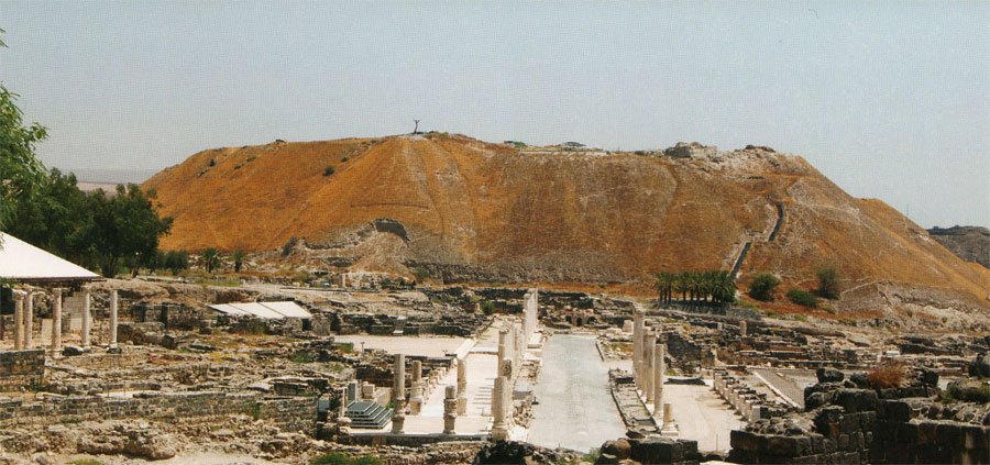"""View looking northeast from the Roman city toward the tell. The dead tree on its summit (just left of center) is a relic of more recent """"biblical"""" events — the suicide of Judas Iscariot in the 1973 film Jesus Christ Superstar . The Roman temple and subsequently the Round Church would have appeared immediately above the end of the colonnaded street."""