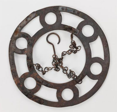 A bronze polykandelon found on the Lower North Terrace, with portions of its suspension chains surviving. Glass lamps filled with oil would have rested in the six round openings. Museum Object Number: 29-108-29