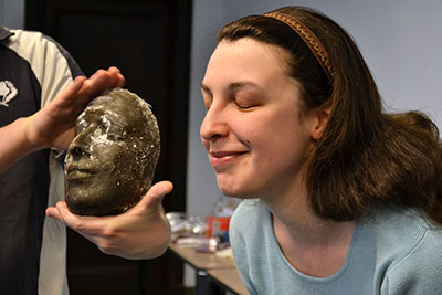 Graduate student Jane Sancinito poses next to her finished mask.