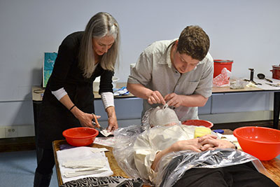 Marianne Lovink works with graduate student Sam Holzman to apply linen strips across the face of a classmate.