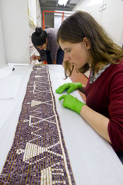 Stephanie Mach and Lise Puyo examining the Two Dog Wampum Belt from Kanehsatake, ca. 1721. Item #M1904 at the McCord Museum in Montreal, Quebec. Photo by Margaret Bruchac.