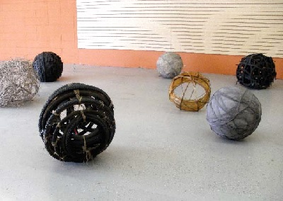 "Spirit Balls, 7 Spheres (2010). 40"" x 15' x 15"", horsehair, dirt, rubber tires, bicycle inner tubes, sticks, and bicycle wheels."