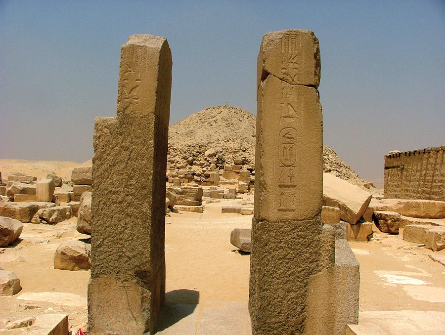Pillars, naming the king Unas, flank the causeway leading to the dilapidated superstructure of the king's pyramid tomb at Saqqara. Photo by Joshua A. Roberson.
