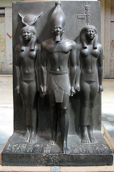 The triad of Menkaure (Giza, 4th Dynasty) shows the pharaoh flanked by two deities: a local nome deity to the right and Hathor to the left. Photo courtesy Wikimedia Commons.