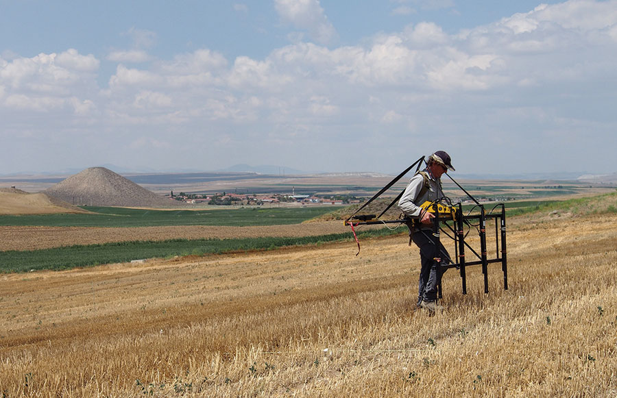 Christian Hübner of GGH uses a magnetometer on the perimeter of Gordion. Tumulus MM is visible in the background. Gordion Archive, photograph by Gebhard Bieg.