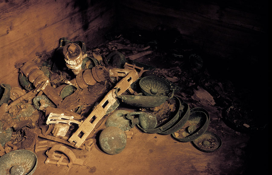The remains of a wooden table and bronze jugs and bowls are shown as they were found in the MM tomb chamber in 1957. Image #G-2366.