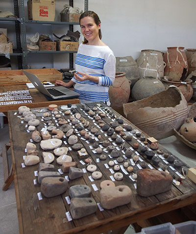 Author Kate Morgan examines spindle whorls and other artifacts associated with spinning, weaving, and sewing that have been excavated at Gordion.