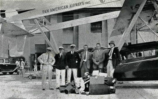 Portrait of men on the aerial expedition in front of their plane
