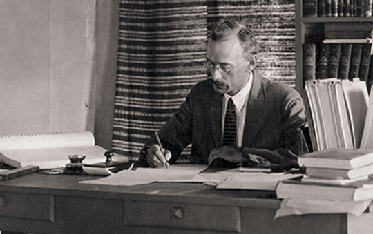 Portrait of Clarence S. Fisher working at his desk
