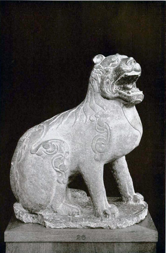 Stone sculpture of a seated line withan open mouth and low relief fur details