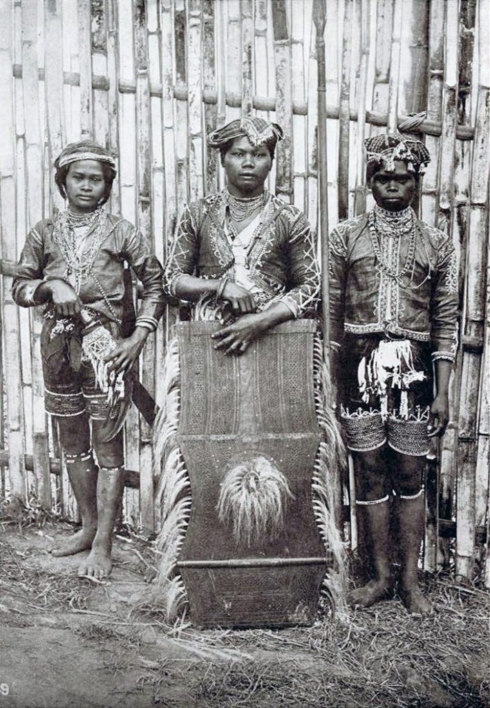 Three warriors in their battle costumes, holding a large shield