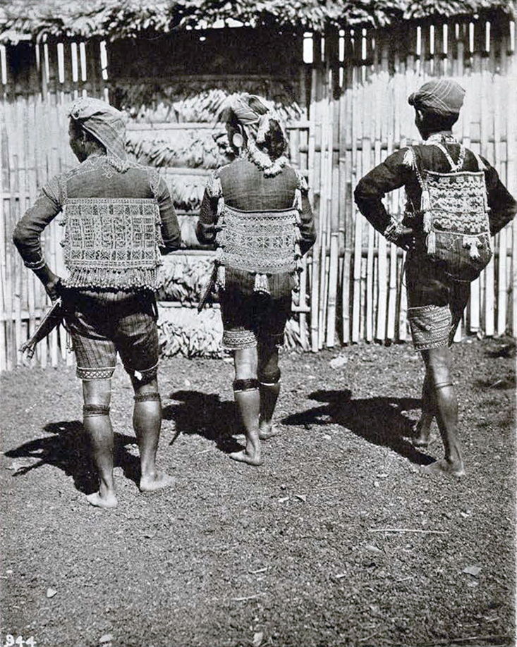 Three men from behind showing detailed embroidery on their pags and shirts